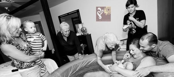 """A beautiful image of a grandma and great-grandma attending the birth of the newest member of their family."""