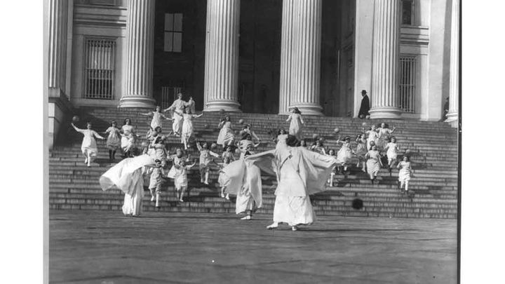 Suffragists and young girls carrying balloons on the steps of the U.S. Treasury, 1913