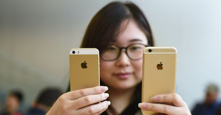 A woman compares two recent iPhones.