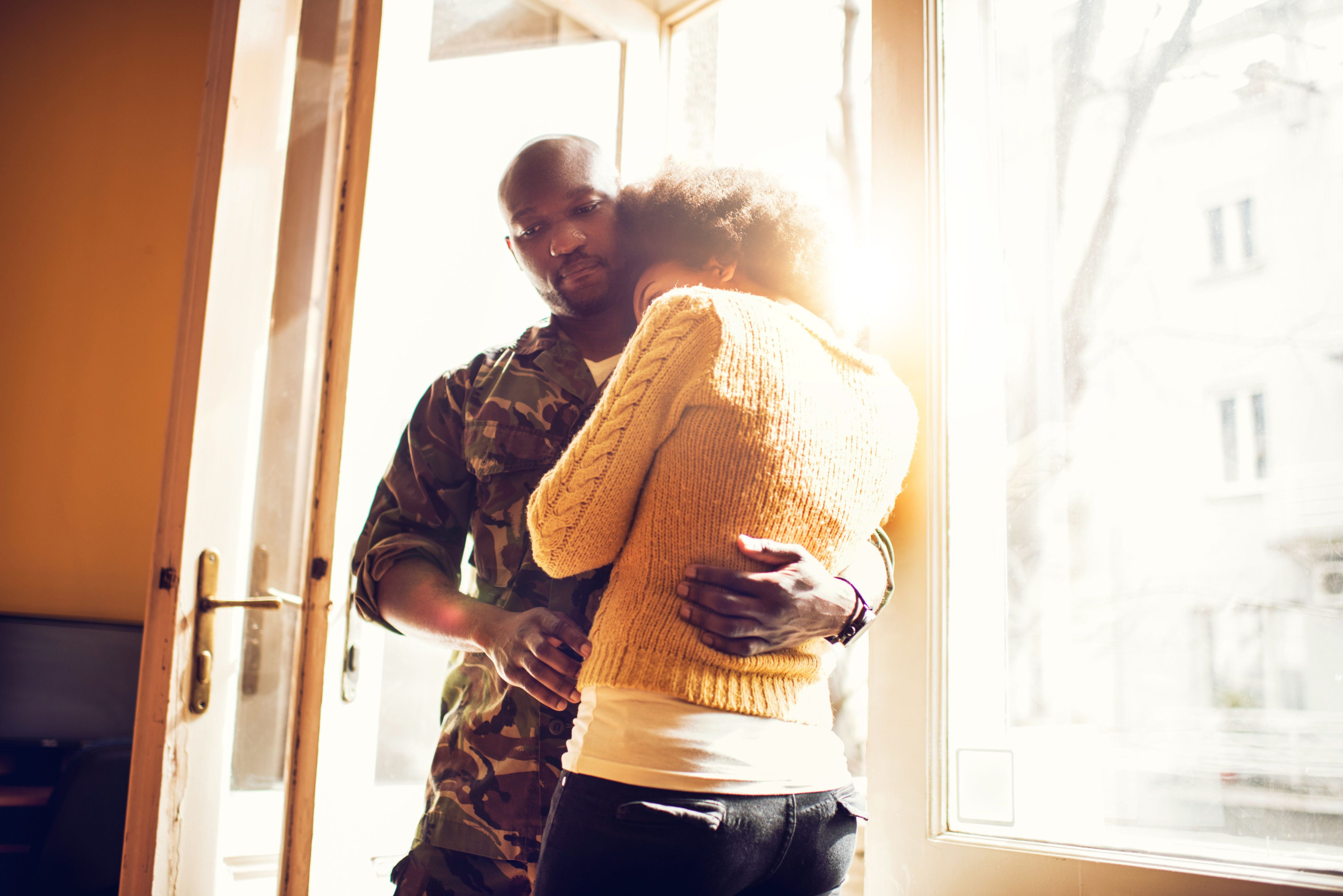 African American couple embracing while military man is about to leave to war.