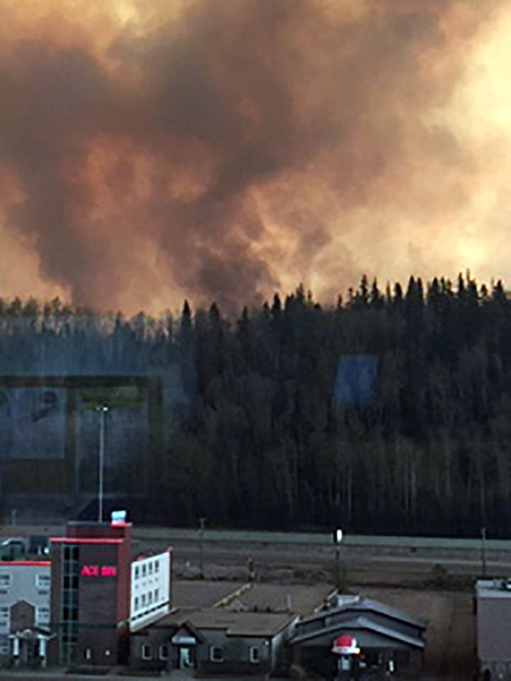 Smoke rises from a wooded area in the Canadian town of Fort McMurray, where wildfires raged on Tuesday.