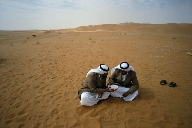 Bedouins of Yam tribe share abowl of water in theRub al Khali Desert,inSaudi