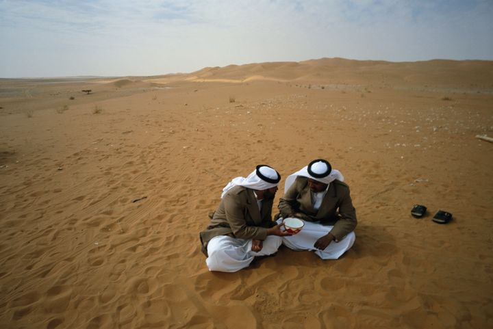 Bedouins of Yam tribe share a bowl of water in the Rub al Khali Desert, in Saudi Arabia.