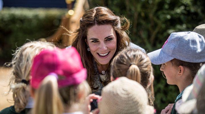 The Duchess of Cambridge talks to local school children at Hampton Court Palace.