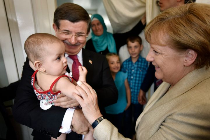 Turkish Prime Minister Ahmet Davutoglu and German Chancellor Angela Merkel pose with a child in a refugee camp on A