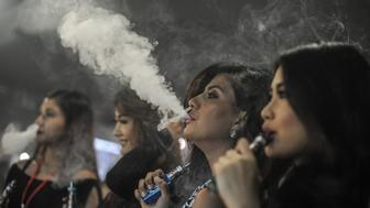 Promoters smoke electronic cigarettes during the VapeFair in Kuala Lumpur on December 5, 2015. Vaping is an alternative to smoke by inhaling water vapour through a vapouriser utilised Propylene Glycol or Vegetable Glycerin based liquid, mixed with small amounts of nicotine and food grade flavoring that then get vaporized in a small battery powered atomizer. AFP PHOTO / MOHD RASFAN / AFP / MOHD RASFAN        (Photo credit should read MOHD RASFAN/AFP/Getty Images)