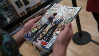 A customer holds a copy of Astonishing X-Men #51 while standing in line to purchase the comic book at a comic book retail shop in Manhattan, New York June 20, 2012. A same-sex couple tied the knot at a comic-book store in New York on Wednesday to celebrate the first gay nuptials in the superhero world in a new edition from Marvel Comics. Midtown Comics delayed the opening of its downtown store for the wedding of Everhart, a healthcare site manager from Columbus, Ohio, and 33-year-old architect Welker. The real-life nuptials, complete with a band, balloons and decorations, coincided with the comic-book union of Jean-Paul Beaubier, aka Northstar, who can move and fly at superhuman speed, and his long-term partner, Kyle, in the series Astonishing X-Men #51.  REUTERS/Adrees Latif (UNITED STATES - Tags: SOCIETY)