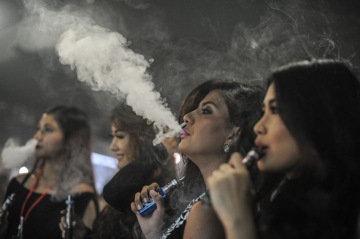 Promoters smoke electronic cigarettes during the VapeFair in Kuala Lumpur on December 5, 2015.