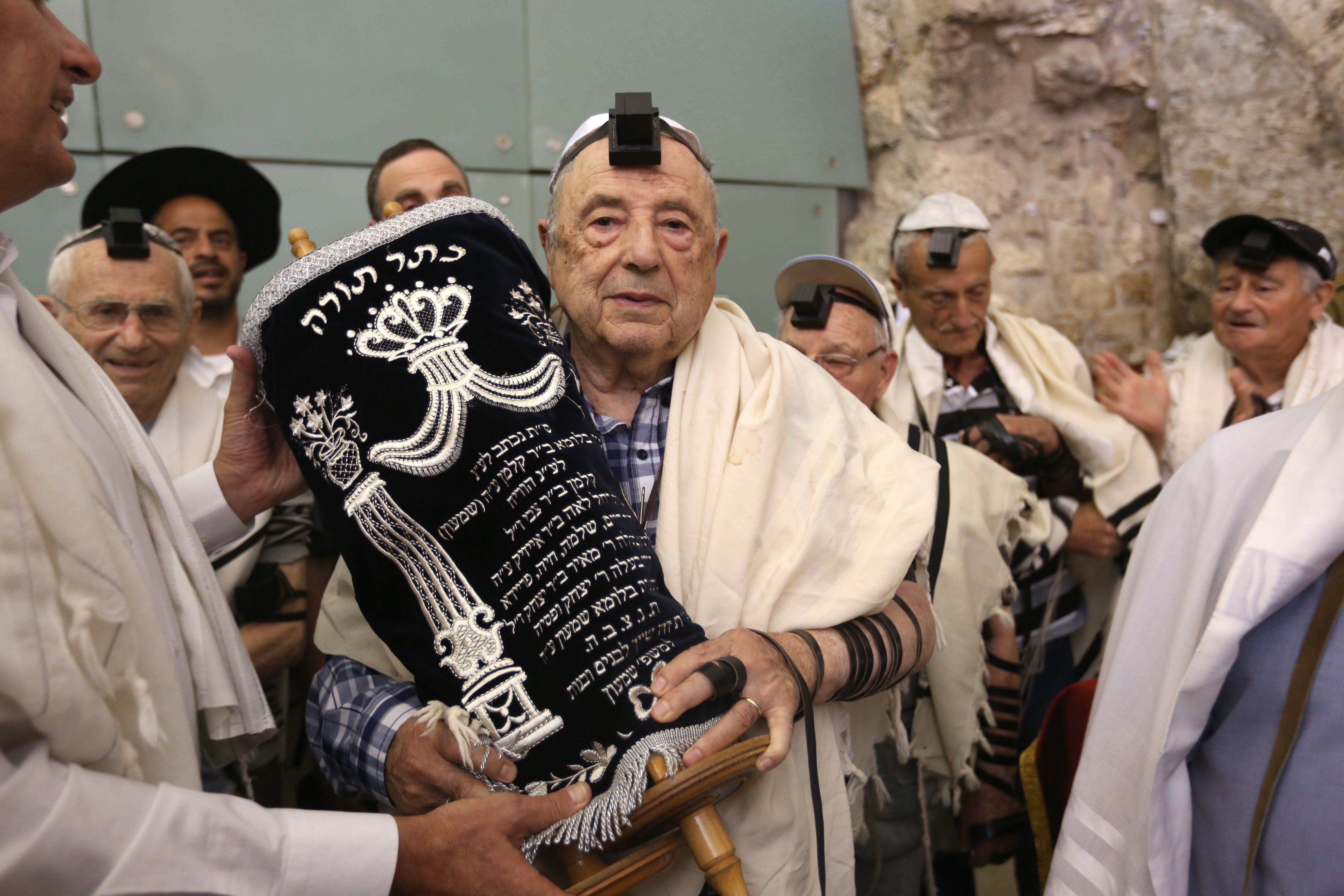 Dozens of Jewish holocaust survivors wear the Tefilin or the Phylacteries and the Tallit prayer shawl as they dance with the Torah after performing their Bar-Mitzvah Jewish ceremony, normally done at the age of 13-years-old, on May 2, 2016, at the Western Wall in the Jerusalem's Old City.  Some 50 male and female holocaust survivors were invited to perform the Jewish Bar-Mitzvah ceremony some 70 years after World War II. / AFP / MENAHEM KAHANA        (Photo credit should read MENAHEM KAHANA/AFP/Getty Images)