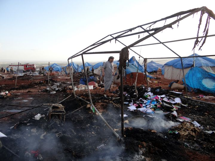 People inspect the damage after airstrikes on the Kamuna refugee camp near the Syrian town of Sarmada on Thursday.