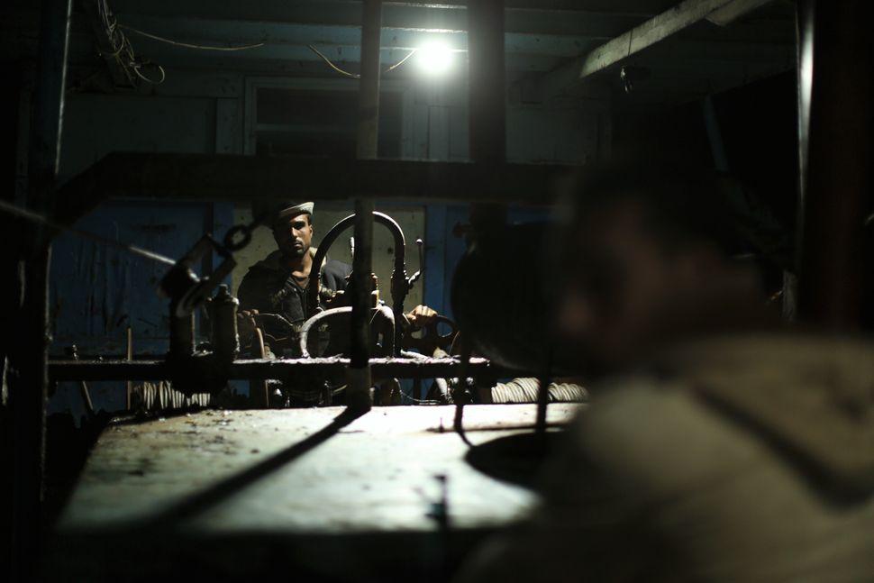 Palestinian fisherman pull out fishing nets usingmechanical levers.