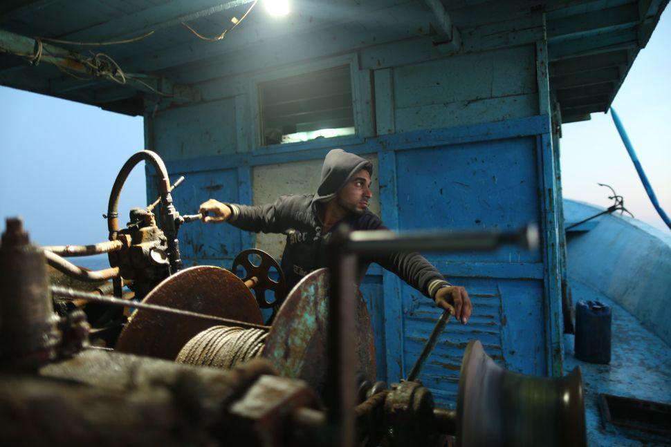 Palestinian fisherman Mohammed Abu Owdapreparesto lift fishing nets withthe ship's levers on April 3. Photo