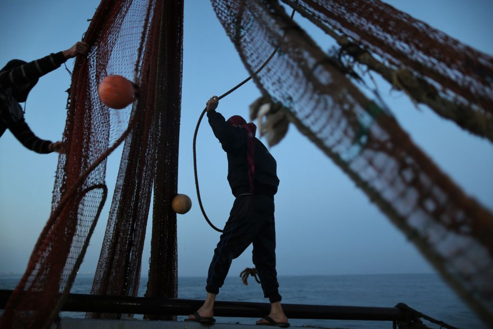 Palestinian fishermen organize their fishing net to make sure that nothing is stuck in it before they throw it back to the se
