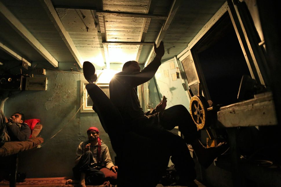 Palestinian fishermen take a rest while the captain of the ship, Raed Abu Owda, tellsstories about hisexperiences