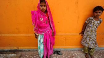 In this Friday, May 6, 2011 photo, a newly married child bride, left, stands at a temple in Rajgarh, about 155 kilometers (96 miles) from Bhopal, India. Ignoring laws that ban child marriages, several young children, are still married off as part of centuries-old custom in some Indian villages. India law prohibits marriage for women younger than 18 and men under age 21. (AP Photo/Prakash Hatvalne)