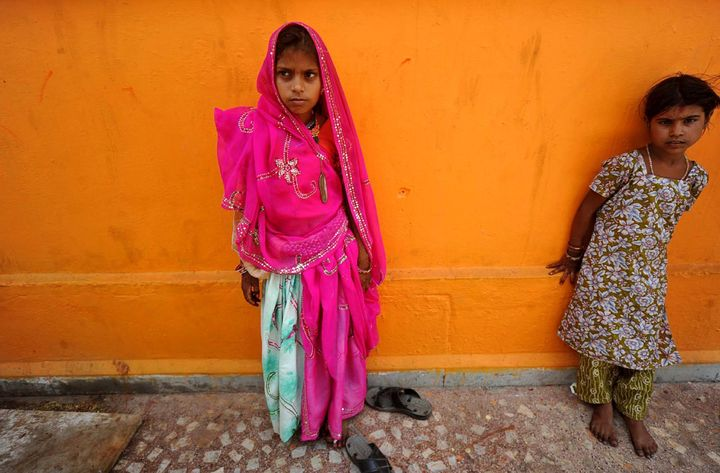 In this Friday, May 6, 2011 photo, a newly married child bride, left, stands at a temple in Rajgarh, about 155 kilometers (96
