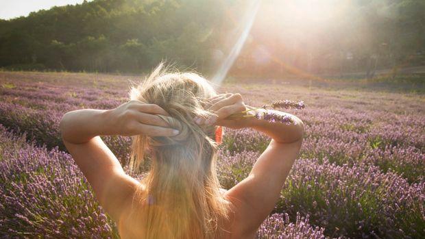 Caucasian woman admiring field of flowers