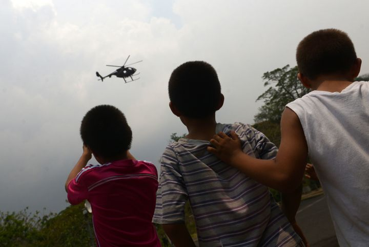 Children watch a helicopter carrying a military unit in Soyapango, El Salvador, on April 26, 2016. El Sal