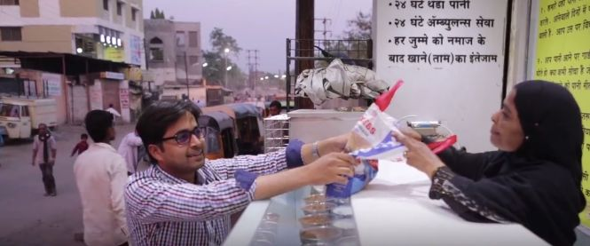 A man depositing food at Roti Bank. (screenshot from AJ+ video)