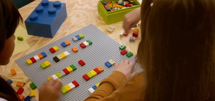 Two kids play with Braille bricks together.