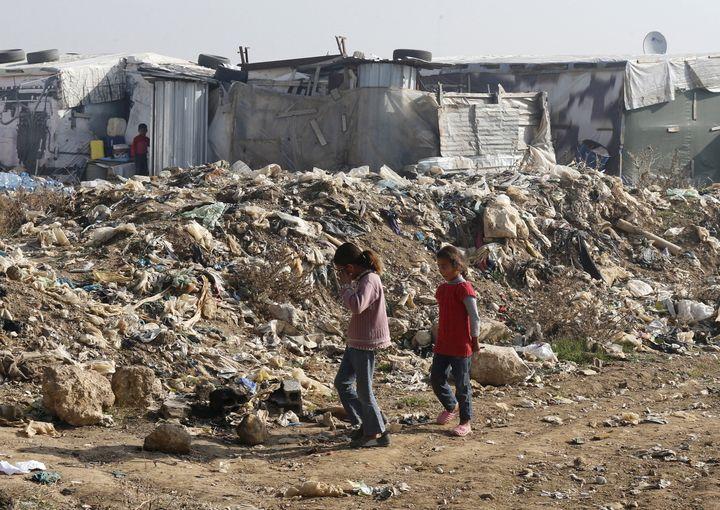 Girls walk near garbage inside Fayda Syrian informal refugee camp in Zahle, Lebanon December 26, 2015. REUTERS/Mohamed Azaki