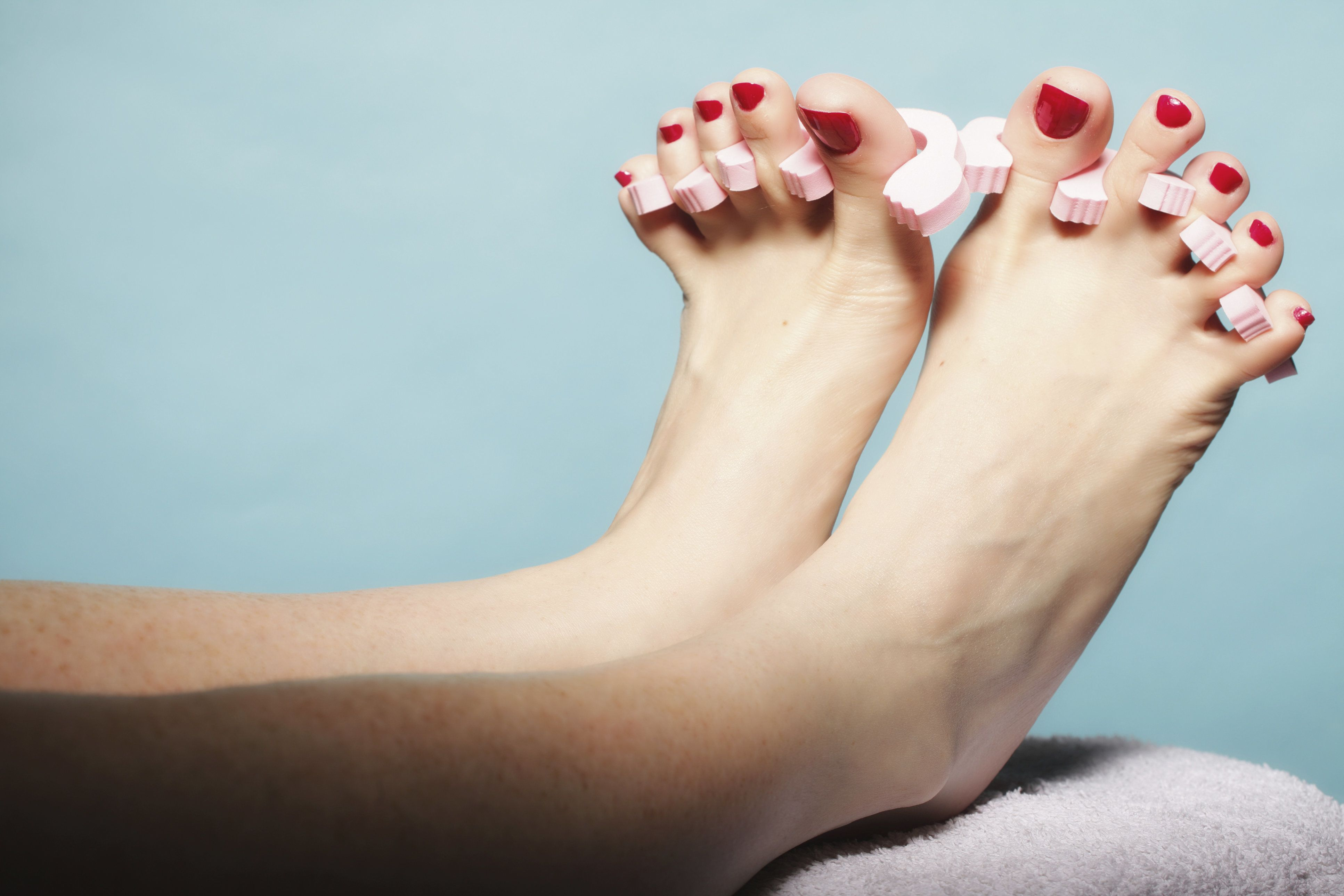 foot pedicure applying woman's feet with red toenails in pink toe separators blue background