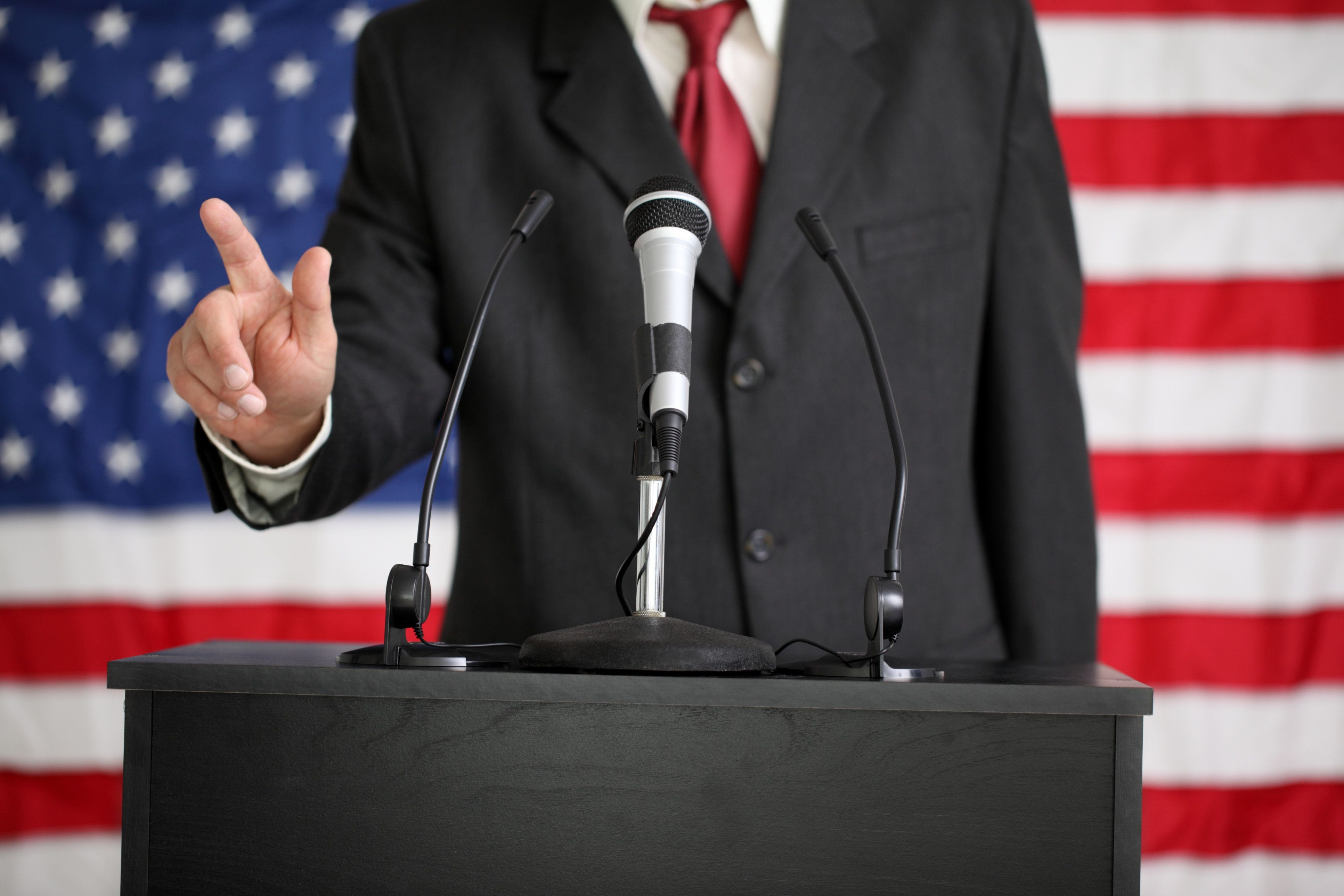 Politician speaking at podium with American Flag in background