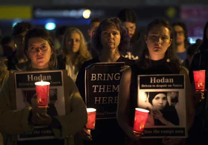 People hold a candlelight vigil in Sydney for two refugees -- a Somali woman and an Iranian man -- who set the