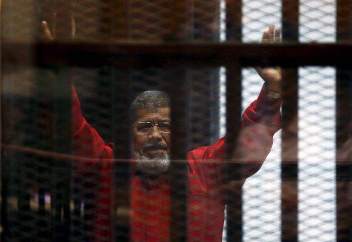 Deposed President Mohamed Mursi greets his lawyers and people from behind bars at a court wearing the red uniform of a prison