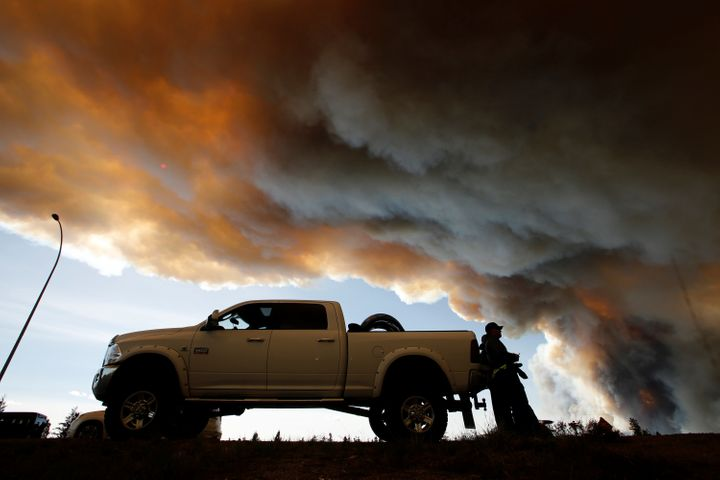 People wait at a roadblock as smoke rises from wildfires near Fort McMurray, Alberta, Canada, May 6, 2016.