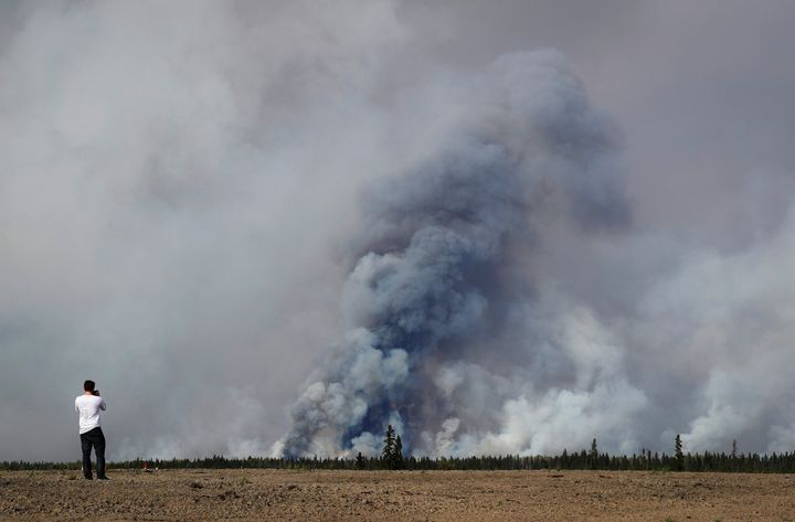 A man takes a photograph of the wildfires near Fort McMurray, Alberta, Canada, May 6, 2016.