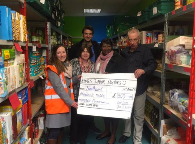 A junior doctor poses with foodbank staff as a cheque for £300 - made up of other medics' donations...