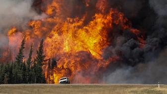 Smoke and flames from the wildfires erupt behind a car on the highway near Fort McMurray, Alberta, Canada, May 7, 2016. REUTERS/Mark Blinch TPX IMAGES OF THE DAY