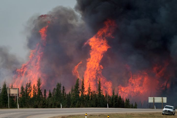 A wildfire burns behind abandoned vehicles on the Alberta Highway 63 near Fort McMurray, Alberta, Canada, on Saturday, May 7,