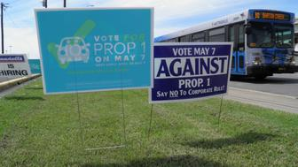 Campaign signs concerning a municipal vote over fingerprint requirements for ride-hailing companies such as Uber and Lyft are seen along a roadway in Austin, Texas, May 6, 2016. REUTERS/Jon Herskovitz