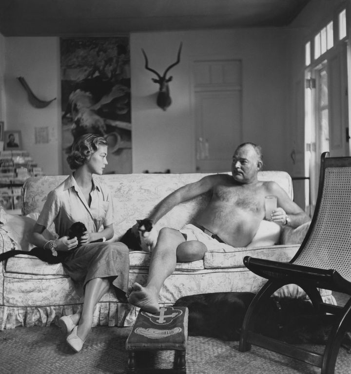Ernest Hemingway pets a cat on a couch in shorts.