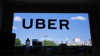 A logo sits on a window inside the offices of Uber Technologies Inc. at Factory Berlin tech hub in Berlin, Germany, on Monday, May 9th, 2016. Uber will start its low-cost UberX service in the German capital next month, according to reports. Photographer: Krisztian Bocsi/Bloomberg via Getty Images