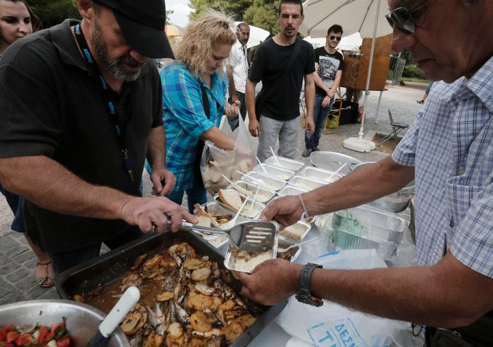 Constantinos Polychronopoulos, left, distributes food portions at a soup kitchen.