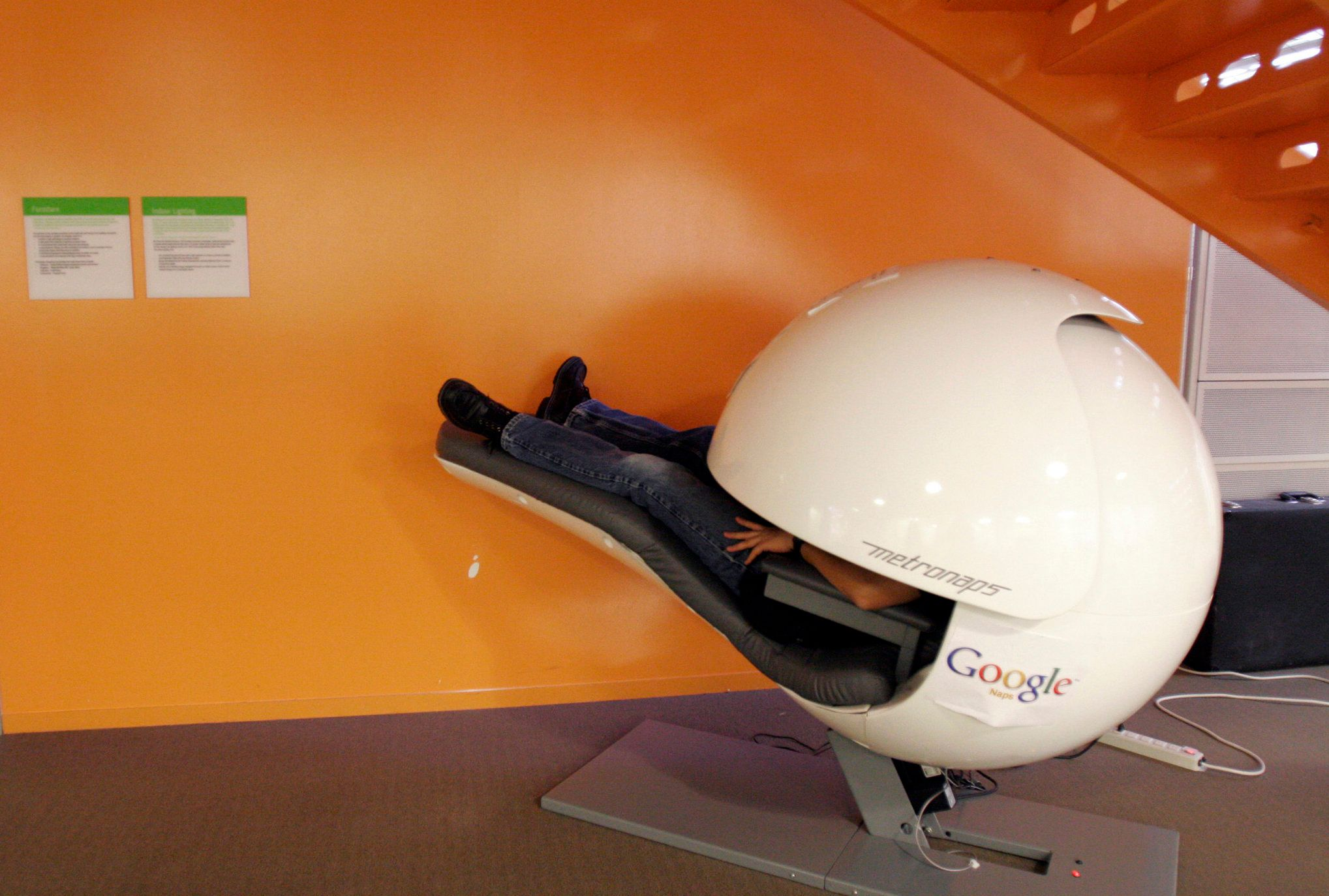 An employee takes a nap in a nap pod which blocks out light and sound at the Google headquarters in Mountain View, California