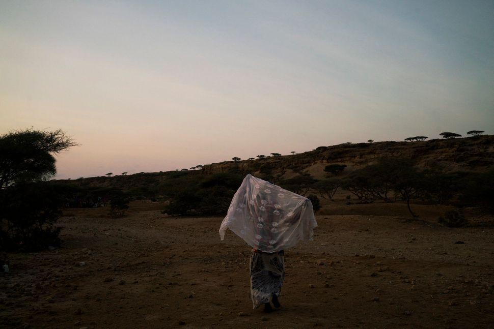 A young Ethiopian girl walks toward a meeting with other migrants and their smugglers in the hope of making it onto one of th