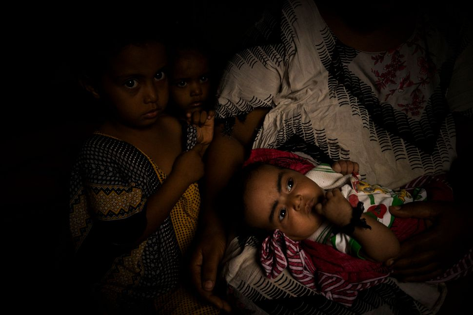 A mother who has fled the war in Yemen with her three children, comforts her baby who is sick and cannot get access to medici