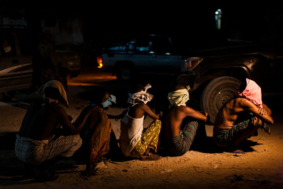 Men believed to be members of al Shabaab sit in the street after being arrested by Somali National Intelligence during a cord