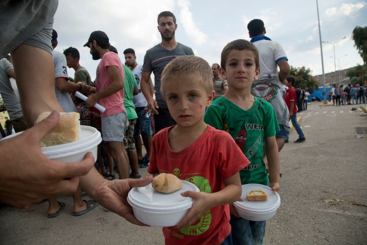 Syrian migrant children hold their food portion at the Kara Tepe refugee camp.