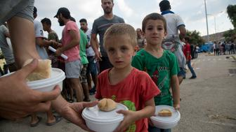 Syrian migrant children hold their food portion at the Kara Tepe refugee camp near the town of Mytilene on the southeastern Greek island of Lesbos, Greece, Friday, Aug. 21, 2015. Greece this year has been overwhelmed by record numbers of migrants arriving on its eastern Aegean islands, with more than 160,000 landing so far. (AP Photo/Visar Kryeziu)