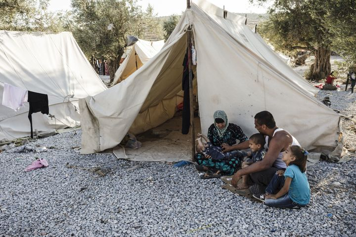 A Syrian refugee family sits outside their tent in the Kara Tepe refugee camp.