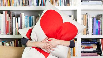 Single woman hugging pillows in living room