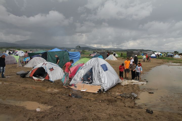 A photo taken at the Idomeni refugee camp on the morning of the ceremony shows the dire conditions endured by the 12,000 peop