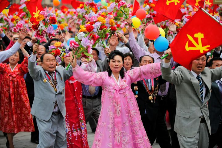 Theywaved pink flowers as they passed before Kimand other top officials on a leaders' platform at Tuesday's parade.