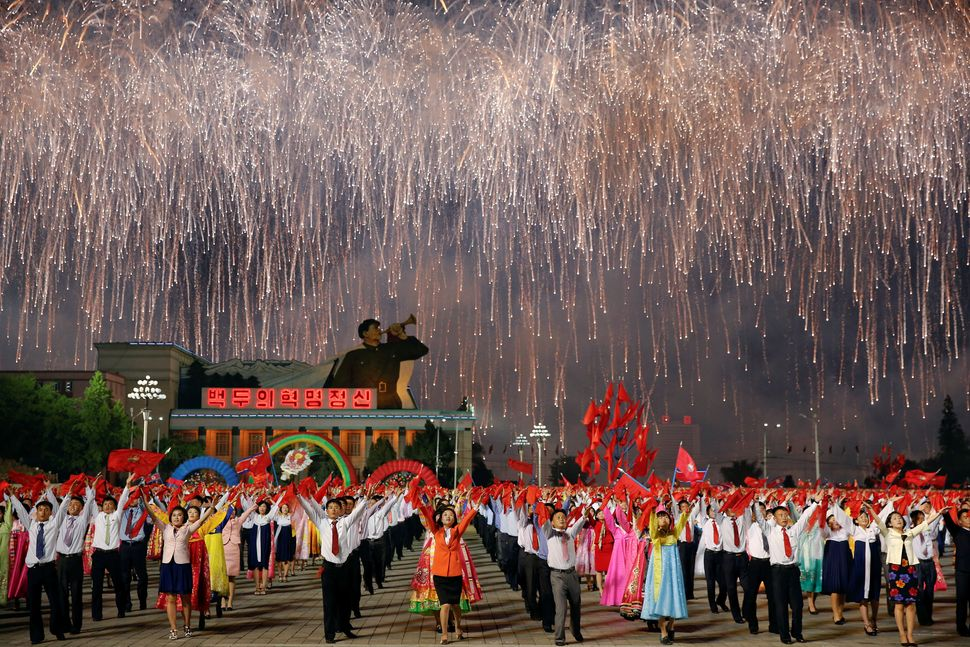 Fireworks explode over a mass dance in the capital's main ceremonial square.