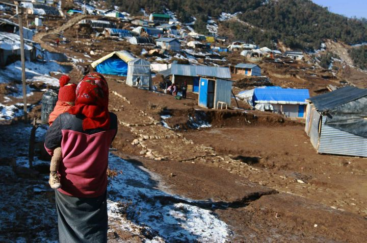 This photo taken on January 21, 2016 shows a Nepalese woman holding a child near temporary shelters in the Nepalese village o